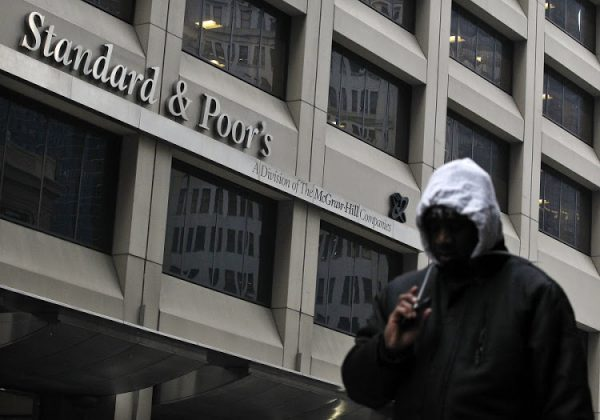 A man walks past the Standard & Poor's building in New York's financial district February 5, 2013. The U.S. government is seeking more than $5 billion in a lawsuit against rating agency Standard & Poor's over mortgage bond ratings, U.S. Attorney General Eric Holder said on Tuesday. The civil suit against S&P and its parent McGraw-Hill Cos Inc is the first federal enforcement action against a credit rating agency over alleged illegal behavior related to the 2007-2009 U.S. financial crisis. REUTERS/Brendan McDermid (UNITED STATES - Tags: BUSINESS CRIME LAW POLITICS) - RTR3DE5O