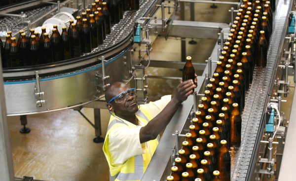 A worker inspects beer bottles on a conveyor belt at the East African Breweries Ruaraka factory in Kenya's capital Nairobi in this February 17, 2010 file photo. Kenya's East African Breweries Ltd (EABL) expects a hike in beer excise duty to hit demand in its home market in the coming months and will raise output of a lower-taxed cheap brand in an attempt to offset the impact, its CEO said on January 29, 2016. REUTERS/Thomas Mukoya/Files